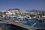 Los Cristianos harbour and the town against the mountains and blue sky. Los Cristianos,Tenerife, Canary Islands, Spain.