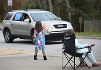 Ansley Sandlin (right), a kindergarten student at Vandergriff Elementary School, waves with her sister Lily, a third grade student, Monday, March 23, 2020, to teachers and faculty in a parade as they drive through the area neighborhood. Students and family members were encouraged to come out and wave from a distance. The teachers were showing their support for the students and expressing how much they miss them. Check out nwaonline.com/2003224Daily/ and nwadg.com/photos for a photo gallery.<br /> (NWA Democrat-Gazette/David Gottschalk)
