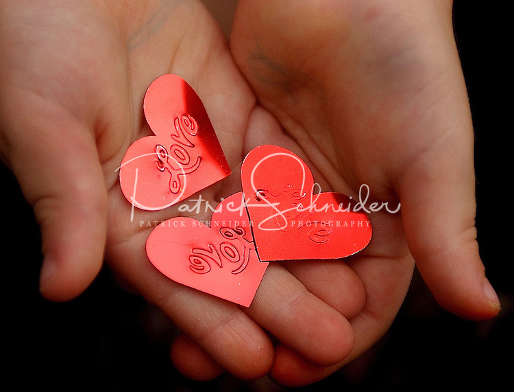 A young boy holds a handful of cut-out hearts for Valentine's Day.