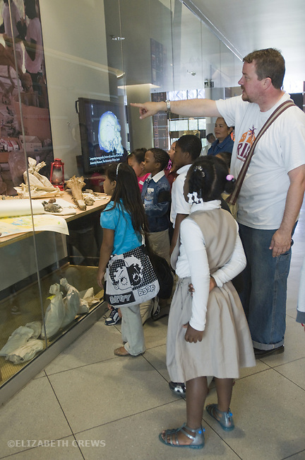 Berkeley CA Second grade teacher pointing out exhibits to students at UC Berkeley Paleontology Museum on school field trip