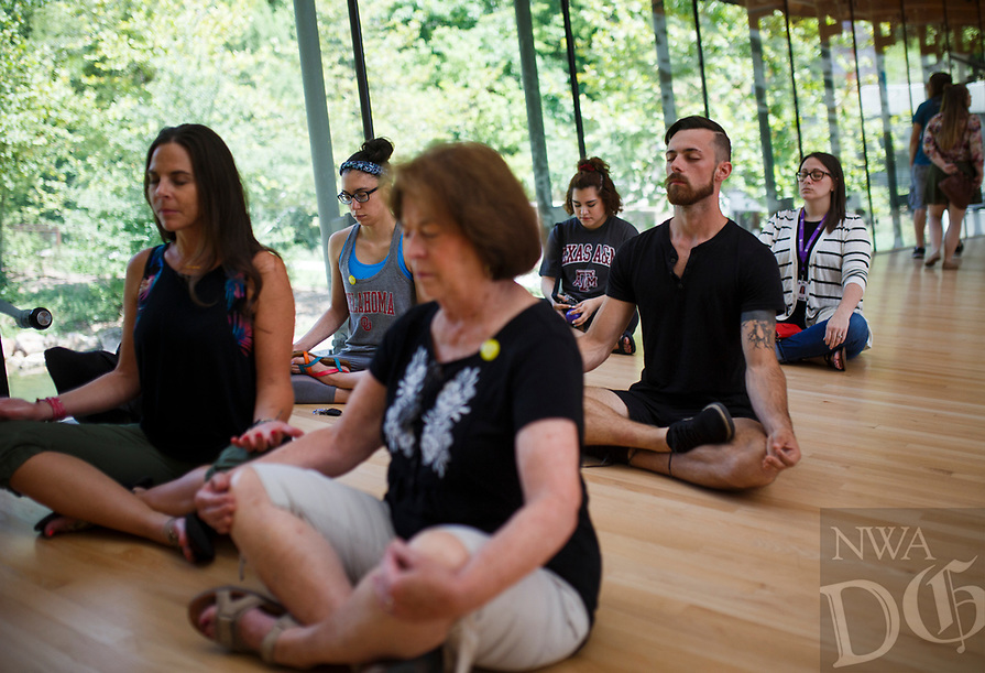 NWA Democrat-Gazette/CHARLIE KAIJO Casey Smith of Fayetteville (center right) and attendees meditate during an art meditation event, Monday, August 6, 2018 at Crystal Bridges in Bentonville. <br />