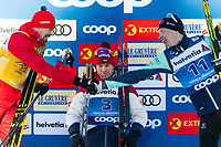 1st January 2020, Toblach, South Tyrol , Italy;  Sergey Ustiugov of Russia and Iivo Niskanen of Finland shake hands in front of Alexander Bolshunov of Russia on the podium after the mens 15 km classic technique pursuit during Tour de Ski on January 1, 2020 in Toblach.