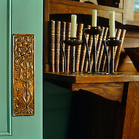 A detail of an Arts an Crafts brass door plate mounted on a turqoise painted door and a row of Arts and Crafts candlesticks in front of a collection of  leatherbound books