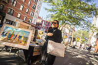A shopper with her TopShop shopping bag in Soho in New York on Saturday, October 10, 2015. (© Richard B. Levine)
