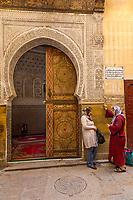 Fes, Morocco.  Women Talking outside Entrance to Zawiya of Sidi Ahmed Tijani.