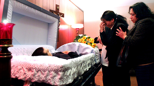 Sandra Zabaleta weeps over her husband's casket during his funeral wake in the chapel at Brooks Funeral Care in Des Moines on Saturday.  Jorge Vides committed suicide after Zabaleta was arrested and jailed for being here as an illegal immigrant.