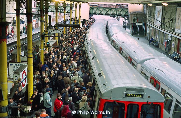 Passengers on the platform of Farringdon underground station, London.