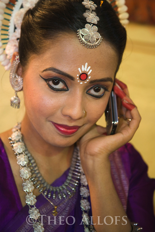 Indian woman in festive sari and make-up on a cell phone;  Varanasi has been a cultural and religious center in northern India for several thousand years, Varanasi, Uttar Pradesh, India --- Model Released