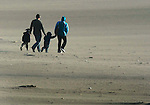 A family of four brave the high winds and blowing sand at Ocean Beach in San Francisco, California.