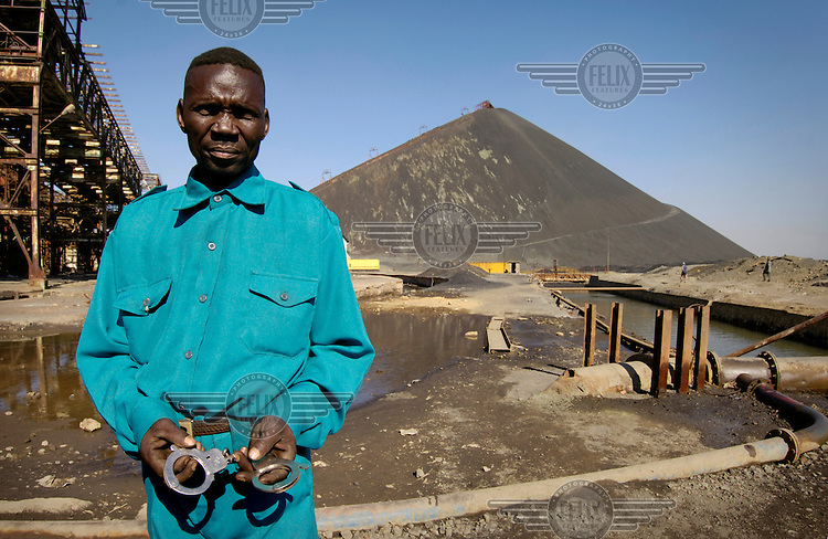 Security guard with handcuffs at 'The Big Hill', a slag heap in the middle of the town made up of waste material left behind by the bankrupt Congolese state owned mining company, Gecamines.  Security is employed at the site in order to prevent the unemployed youths of the town scavenging among the waste for copper to resell..