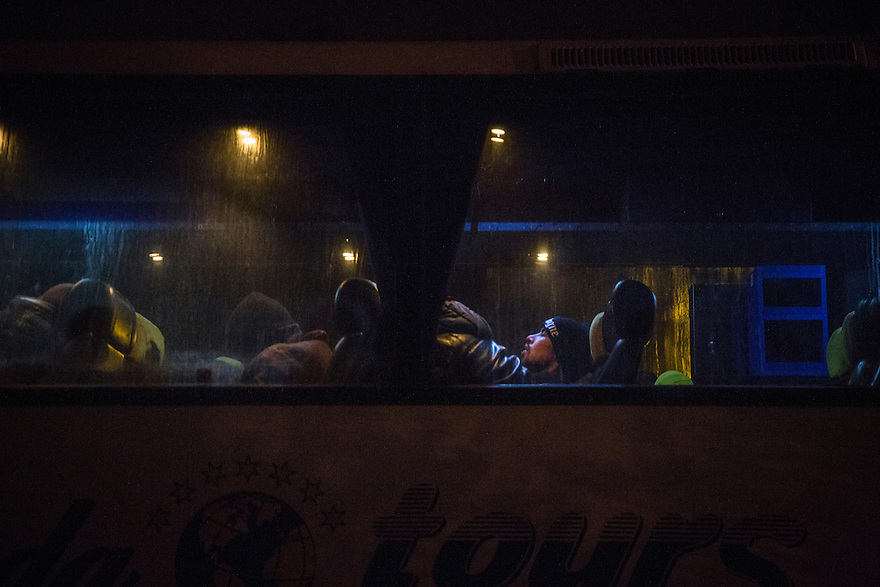 Dimitrovgrad, Serbia-- December 16, 2015--Afghan immigrants wait in a bus bound for Belgrade after arriving in Serbia after midnight. The bus was still at the station the following day, more than 12 hours later, waiting to fill the bus before making the trip.