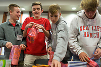 NWA Democrat-Gazette/CHARLIE KAIJO Collin Krapf, 15 of Bentonville, Cooper Mackey, 15 of Bentonville, Walker Pool, 14 of Bentonville and Alexander Apolskis, 14 of Bentonville make gift bags on Sunday, November 12, 2017 at the Circle of Life Hospice meeting room in Bentonville. Ninth and tenth grade boys from the Ozark Chapter of Young Men's Service League created care packages to send to a troop of 50 soldiers stationed in Kandahar, Afghanistan. Immediately prior to the service project, they heard firsthand experiences from a military veteran who was stationed in Kandahar.