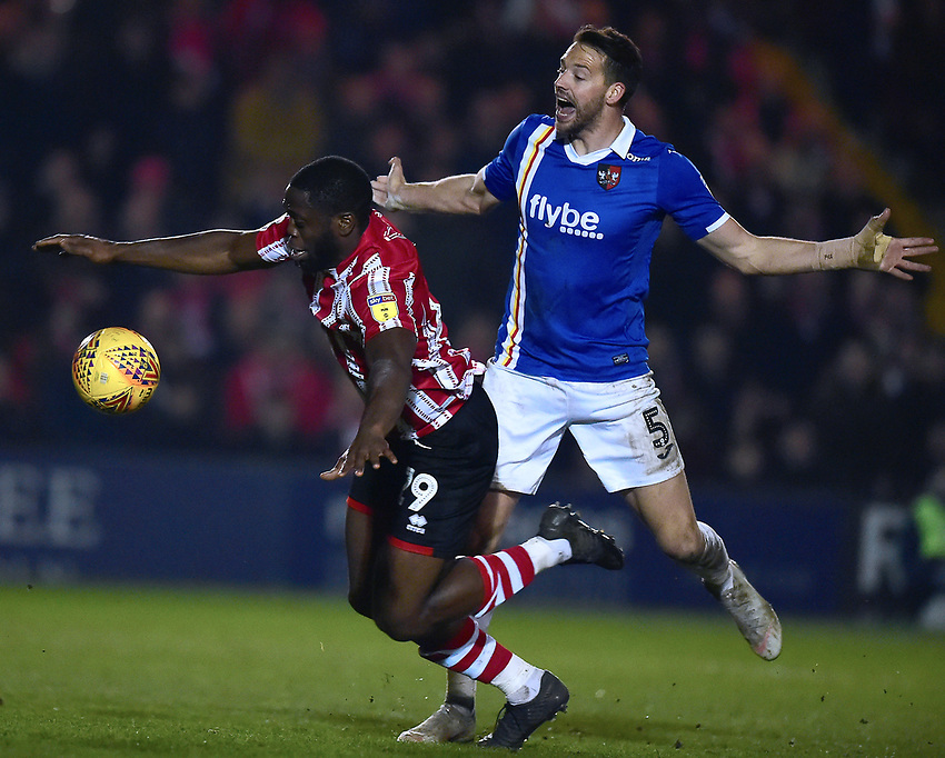 Lincoln City's John Akinde goes down under pressure from Exeter City's Aaron Martin, only for a penalty appeal to be turned down<br /> <br /> Photographer Andrew Vaughan/CameraSport<br /> <br /> The EFL Sky Bet League Two - Lincoln City v Exeter City - Tuesday 26th February 2019 - Sincil Bank - Lincoln<br /> <br /> World Copyright © 2019 CameraSport. All rights reserved. 43 Linden Ave. Countesthorpe. Leicester. England. LE8 5PG - Tel: +44 (0) 116 277 4147 - admin@camerasport.com - www.camerasport.com
