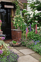 "Front entrance of old house with black door, stone walkway path, flower & herb garden, honeysuckle and clematis vines, Spanish lavender herb, flowers and herbs interplanted, trees, name sign of ""The Cottage"", trug of herb plants for inviting welcome, Flowering Dogwood Venus hybrid made from C. kousa × nuttalli x kousa"