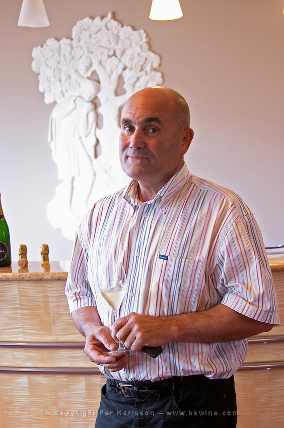 Serge Lefevre, president of Union Champagne, in front of a sculpture showing the grape harvest and holding a glass of de Saint Gall champagne, the Union Champagne cooperative, also called Champagne de Saint Gall in Avize, Cote des Blancs, Champagne, Marne, Ardennes, France