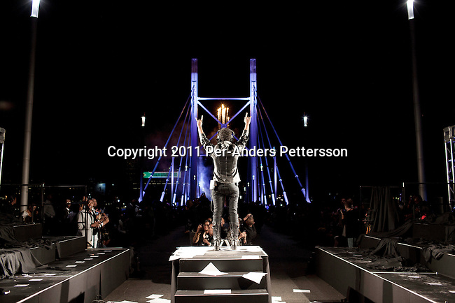 JOHANNESBURG, SOUTH AFRICA - FEBRUARY 19: The designer David Tlale, watches as his 92 models walk on the Nelson Mandela Bridge at the Joburg Fashion Week on February 19 2011, in Johannesburg, South Africa. David Tlale, is an award winning designer and one of South Africa's finest designers, dressing celebrities and others in couture with elegance and high quality material. He held his show at the Mandela Bridge in downtown Johannesburg. A logistical nightmare, the bridge was closed and turned into a  catwalk at midnight with hundreds of people watching the show. 92 models, one for each of Nelson Mandela's years walked the 285 meter bridge, maybe the longest catwalk in the world. South African top designers with showed their 2011 Autumn & Winter collections during the 5 day event. (Photo by Per-Anders Pettersson)
