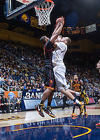 California's Kameron Rooks tries to shoot for the basket defended by USC defender during a game at Haas Pavilion in Berkeley, California on February 23th, 2014. California defeated USC 77 - 64