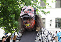 A man participating in the Zombie Walk in Prague, wearing a mask with yellow teeth, and having another mask in his forehead. Wearing a dark blue T-shirt and a white and blue check pattern.