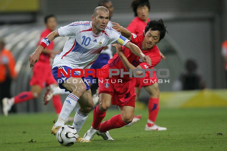 FIFA WM 2006 -  Gruppe D  Vorrunde ( Group D )<br /> Play   #29 (18-Jun) - Frankreich - Korea 1:1<br /> <br /> Zinedine Zidane (links) von Frankreich im Zweikampf mit <br /> Nam II Kim (rechts) von Korea.<br /> <br /> Foto &copy; nordphoto