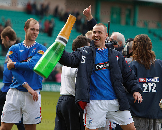 Kenny Miller celebrates winning the SPL championship with a large bottle of bubbly