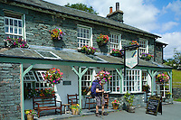 Walker at Three Shires Inn public house at meeting point of Cumberland, Lancashire and Westmoreland at Langdale in Lake District National Park, Cumbria, UK