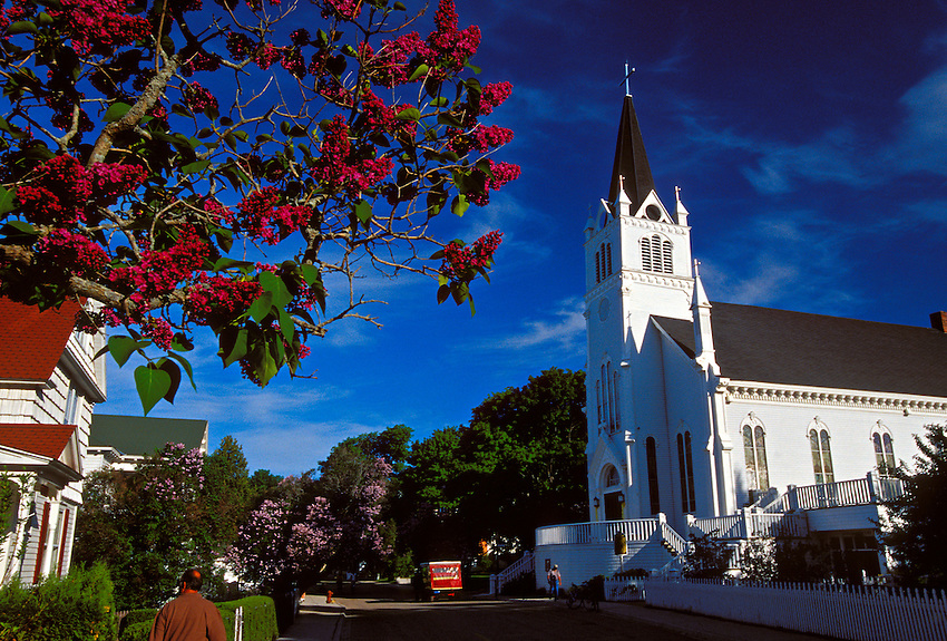 A CHURCH AND BLOOMING LILACS AT MACKINAC ISLAND, MICHIGAN.