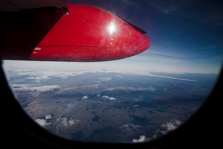 The coastal strip of 'dry' Greenlandic soil, and ice cap at the horizon, are viewed from the window of a Dash-7 flight, West Greenland, August 2011. Photo: Ed Giles.
