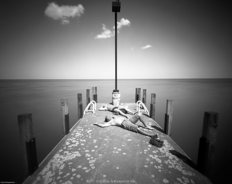 Sunbathers lie atop a pier near a boat launch on Lake Erie in Bay Village, Ohio.