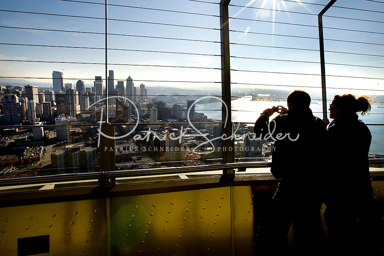 Tourists snap pictures from the top of the Space Needle in Seattle Washington.