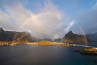 Autumn rainbow fills sky over Reine and surrounding mountains, Moskenesøy, Lofoten Islands, Norway