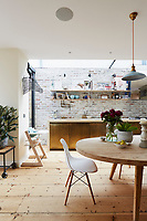 The kitchen is an impressive, open-plan space incorporating a dining table and chairs. The kitchen cupboards are custom-built by Bert & May and an exposed brick façade, painted to look old, adds an industrial vibe to the kitchen. The kitchen chairs are Eames DSW.