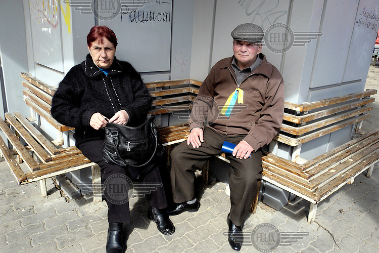 An elderly couple rest following a rally in support of Ukrainian unity held on the 40th day after the deaths of many protestors in clashes with security forces in Kiev. Events that led to the collapse of the ruling Party of the Regions and the ousting of President Viktor Yanukovych. The ribbon worn by the man is in the colours of the Ukrainian flag and shows his support of a united Ukraine. Protests against the government of President Viktor Yanukovych were sparked on 21 November 2013 by the Ukrainian government's decision to suspend preparations for the signing of an association agreement with the European Union that would have increased trade with the EU. Some believe that the U-turn came about as a result of pressure from President Putin of Russia who wants Ukraine to join a customs union with itself, Kazakhstan and Belarus. Russia offered 15 billion dollars of soft loans and reduced price gas to Ukraine at the same time as discussions with the EU were taking place. After weeks of protests and a number of deaths, Prime Minister Mykola Azarov and the entire cabinet resigned. On 18 February, after Yanukovych's party scuppered a move to change the constitution to reduce the powers of the president, renewed fighting between protesters and police broke out and had cost the lives of around 80 people by Friday 21st February. By 22 February Yanukovych had fled Kiev. In the days following the Ukrainian parliament decided to strip him of the presidency.