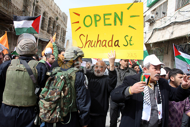 Israeli police officers try to push back Palestinian, Israeli and foreign activists during a protest against the continued closure of Shuhada street to Palestinians, in the West Bank city of Hebron 25 February 2011. The activists gathered on Friday calling for the end to the closure of Shuhada street, which was closed by the Israeli army in 1994 following the Hebron mosque massacre by Baruch Goldstein, an Israeli settler, who went on a rampage inside Al Ibrahimi Mosque, killing 29 Palestinian worshippers.. Photo by Najeh Hashlamoun