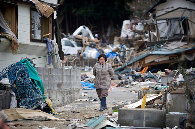 Yoko Abe walks past the wrecked remains of her family's home at Imeshi village on the Oshika Peninsula, Miyagi Prefecture, Japan on 19 March, 2011.  Photographer: Robert Gilhooly