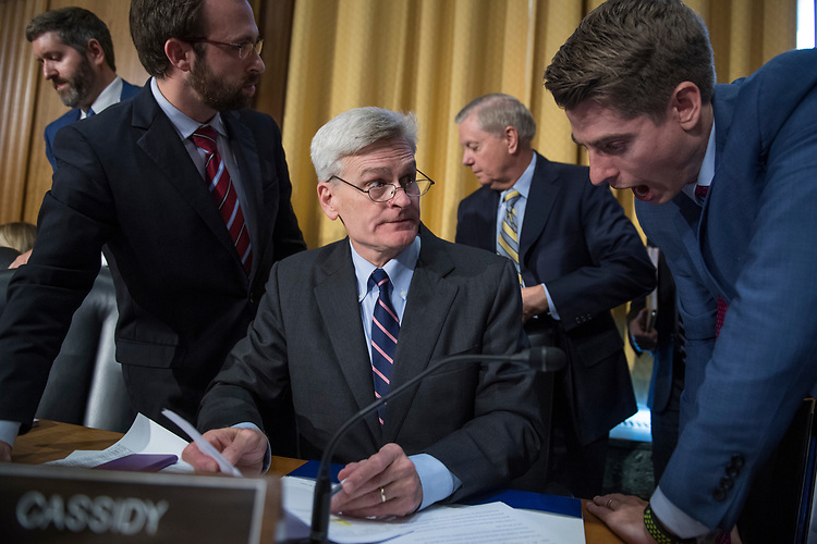 UNITED STATES - SEPTEMBER 25: Sen. Bill Cassidy, R-La., talks with staff as Sens. Lindsey Graham, R-S.C., in the background, leaves the room, after protesters caused a recess in the Senate Finance Committee hearing on their proposal to repeal and replace the Affordable Care Act, on September 25, 2017. (Photo By Tom Williams/CQ Roll Call)