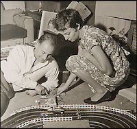 BNPS.co.uk (01202 558833)<br /> Pic: PhilYeomans/BNPS<br /> <br /> Stirling Moss plays with the original Scalextric.<br /> <br /> Blast from the past - 56 year old box of the very first Scalextric finally handed over to inventors daughters.<br /> <br /> The dying wish of Scalextric inventor Freddie Francis has been granted - after his daughters were gifted an original mint set that has been in storage for the past 50 years.<br /> <br /> Freddie and his widow Diane boxed up the original set shortly before he died in 1998 and Diana has waited till now before handing the valuable heirloom over.<br /> <br /> The previously unopened set has been preserved in a wooden box at the Francis family home until now.<br /> <br /> The historic set contains 1950's Ferrari and Maserati style racing car's that would have been driven by Fangio and Stirling Moss and even includes oil to keep the cars running and silicone for 'skid patches'.<br /> <br /> Although the set cost &pound;5 in 1957, it's worth well over &pound;1500 today.