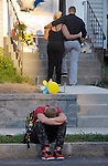 An emotional David Haddock, 16, of Enfield, sits in front of the sidewalk where his friend Jonathan Torres was shot and killed less than 24 hours earlier, as others visit the make shift memorial on the steps to his house, Thursday evening, prior to a large candle light vigil, on Prospect Street in the Thompsonville scetion of Enfield. (Jim Michaud / Journal Inquirer)