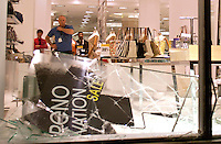 Store employees at Hudson's Bay Company in downtown Vancouver,BC look on helplessly as rioters smash windows and burn cars in the street after the Canucks were defeated by the Boston Bruins in the Stanly Cup on June 15, 2011. (photo copyright Karen Ducey)