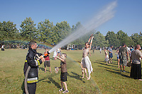Children cool down themselves in the water spray of a fireman during .People dressed in period costumes participate in the 6th Arrow Rain event celebrating Hungarian war traditions in Opusztaszer, Hungary on June 30, 2012. ATTILA VOLGYI