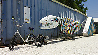 A trike hooked up to a trailer hauling a sculpture of a fish skeleton filled with trash at the FROG stop along the Los Angeles River Greenway Trail.  The FROG stop is hosted by the Friends of the Los Angeles River (FoLAR), and has food wand water for trail users.