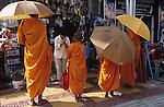 CAMBODIA, city Phnom Penh, buddhist monks in orange robe with umbrella collecting alms in chinese quarter / Kambodscha Phnom Penh, buddhistische Moenche in orangenen Roben mit Sonnenschirm sammeln Almosen in Chinatown