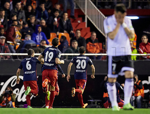 06.03.2016. Mestalla Stadium, Valencia, Spain. La Liga match between Valencia versus Atletico Madrid.  Midfielder Midfielder Carrasco of Atletico Madrid (2nd R) celebrates with his team mates while Forward Alvaro Negredo of Valencia CF (R) reacts dejectedly