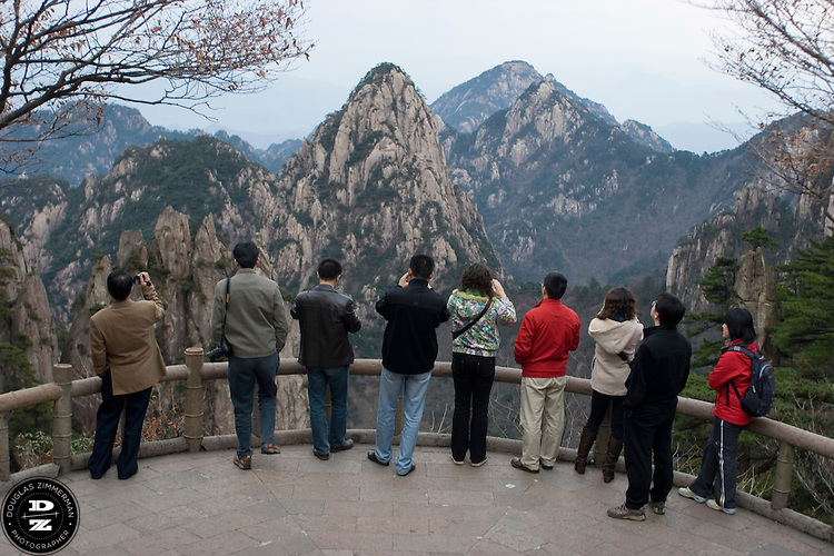 A group of tourists take photographs of some of the the granite peaks and twisted pine trees on top of Hung Shan mountains in Hung Shan, China.  The mountains are some of the most beautiful scenery in China.  Photograph by Douglas ZImmerman