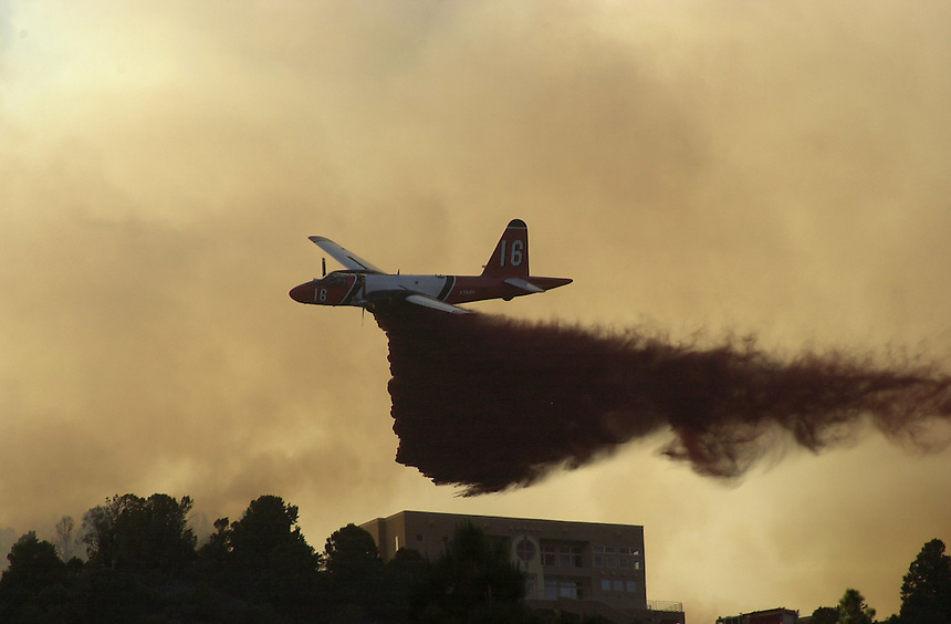 A slurry tanker firefighting aircraft drops a load of fire retardant near a home in Durango, Colorado in June, 2002.