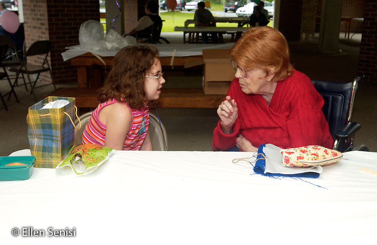 MR / Schenectady, NY.Yates Arts-in-Education Magnet School (urban elementary school) .Grade 4.Girl (11) talks with elderly woman on field trip to nursing home.  She has corresponded with her monthly throughout the school year as part of a year-long partnering project which combines reading, history, and writing activities with community awareness. This is the partners' first meeting at end of the school year. .MR: Arm3   Bra8.© Ellen B. Senisi