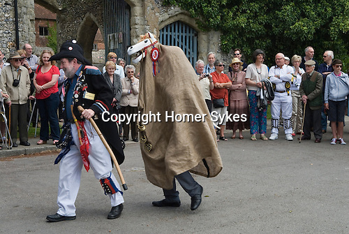 Hooden Horse East Kent Morris Men. The Steward who introduces the performances in the square outside the church of St Peter and St Paul Charing Kent UK. Spring Bank Holiday Monday. David Rivers inside Invicta the Hooden Horse, so called after the emblem of Kent.