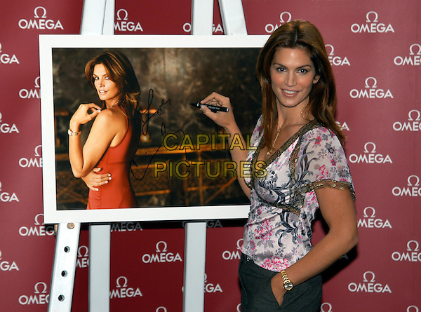 CINDY CRAWFORD.at launch of Omega watch campaign.half length half-length floral flower print lace-trim top, v-neck, floaty, signing autograph picture photograph.sales@capitalpictures.com.www.capitalpictures.com.©Capital Pictures