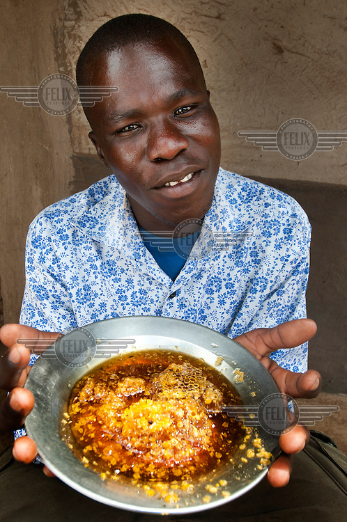 Tony, a disabled, former abductee of the Lord's Resistance Army, holds up a plate of freshly harvested honey a product of an apairy group of which he is a member.