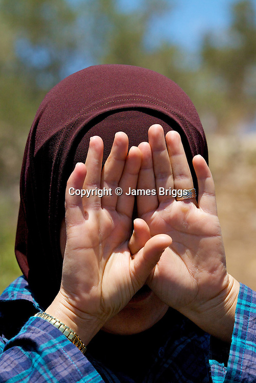 A Palestinian woman hides her face from an (unseen) Israeli army photographer during a demonstration in the village of Nabi Saleh near Ramallah on 02/07/2010.