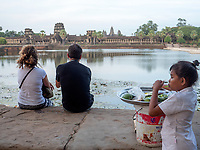 Tourists at Angkor Wat, Cambodia while a local vendor is looking on